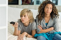 Teenage boy watching television with a girl sitting beside him