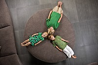 Three friends lying on a round sofa