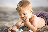 Baby boy playing with shells in sand