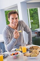 Portrait of a man having breakfast and smiling