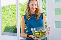 Portrait of a woman holding salad in a mixing bowl and smiling