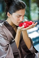 Woman smelling rose flowers (thumbnail)