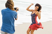 Man making a video of a dancing woman on the beach