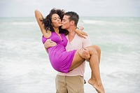 Man carrying and kissing a woman on the beach (thumbnail)