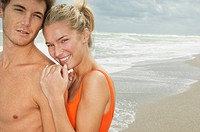 Portrait of a couple smiling on the beach (thumbnail)