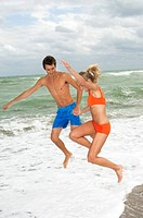 Couple holding hands and jumping on the beach