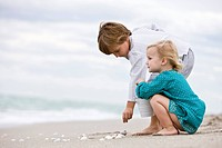 Boy and his sister playing with shells on the beach