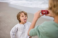 Boy taking his brother's picture with a digital camera