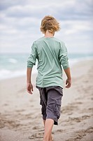 Rear view of a boy walking on the beach