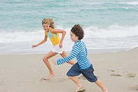 Boy running with a girl on the beach (thumbnail)