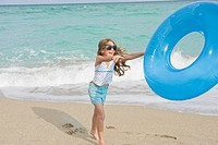 Girl playing with an inflatable ring on the beach
