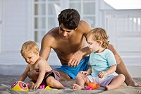 Man playing with his son and daughter in sand