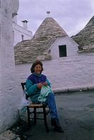 Photograph of an Italian woman sitting and knitting