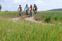 Couples riding bicycles on rural path