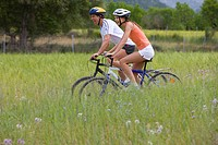 Couple riding bicycle through rural field