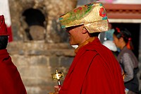 Tibetan Buddhism, Kora pilgrim, monk dressed in red robes with a golden cap and a prayer wheel on the road to the Barkhor, Jokhang Temple, Lhasa, Hima...