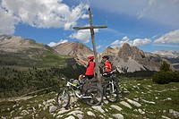 Mountain bike riders having a rest stop on a wooden bench in front of a wooden cross on the Limo Pass in Fanes-Sennes-Prags Nature Park, Trentino, Alt...