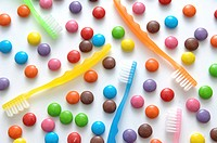 Colorful chocolate candies and toothbrushes