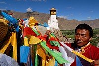 Young Tibetans in traditional costume hang up prayer flags above the Yarlung valley, Yumbulagang palace, first and oldest fortress of Tibet, Central T...