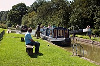 Man sat on rustic bench watching narrow boar enter Lock 68 on Kennet and Avon Canal