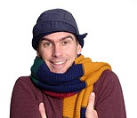Young man feeling the cold, wearing a big colourful scarf and winter hat