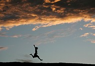Woman jumping in front of the sunset, Wave Rock, Hyden, Western Australia, Australia