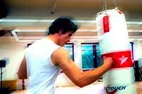 young man in sportswear striking a box pear, sand bag