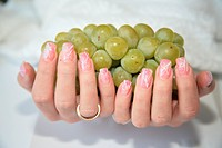 Hands holding grapes, finger nail art