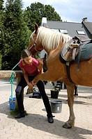 girl saddling horse.