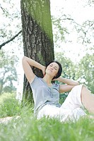 woman relaxing under tree