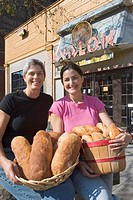 Detroit, Michigan - Jackie Victor in pink and Ann Perrault, owners of Avalon International Breads, hold some of their products outside their bakery