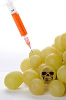 Syringe in grapes, symbolic image for genetically modified foods