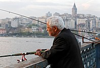 White haired Turkish angler on the Galata Bridge, evening sun, Eminoenue, Istanbul, Turkey