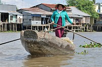Woman with traditional hat, cone-shaped hat made of palm leaves, standing and rowing a wooden boat on the Mekong, load of fruit and vegetables, Mekong...