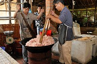 Two men with large wooden spoons stirring in a bowl while preparing puffed rice sweets, confectionery factory, Vinh Long, Mekong Delta, Vietnam, South...