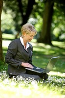 Woman wearing a ladies´ suit, trouser suit, businesswoman, early 40s, working on her laptop in a park