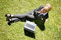 Woman wearing a ladies' suit, trouser suit, businesswoman, early 40s, working on her laptop in a park, on her mobile
