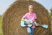 Young girl leaning on bale of hay playing guitar.
