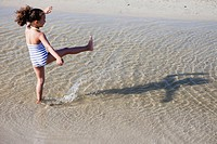 young girl playing in water at beach