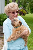 mature woman hugging her brussels griffon dog