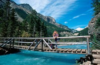 woman standing on a wooden bridge over river, Canada, Alberta, Banff NP