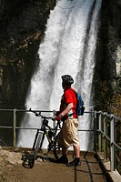 Biker marvels at the thundering waterfalls of Rinquelle, Rin Spring, and Seerenbach, Betlis, St. Gallen, Switzerland, Europe