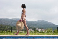 Young Woman Walking by Pool