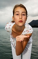 Young girl at a lake, blowing a kiss
