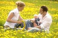Family sitting in a spring meadow