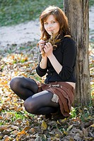 Attractive young woman with Autumn leaves in hands