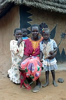 Dinka woman with her children in front of mud house, Sudan