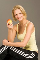 Young blond woman wearing sports clothing, holding an apple in her hand