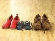 three pairs of shoes on parquet