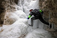 Ice climber on a frozen waterfall in the Kalkalpen National Park, Upper Austria